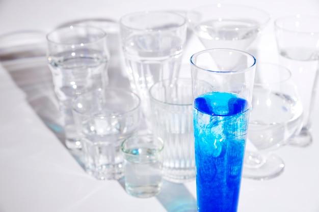 Голубые чернила растворяются в воде внутри стекла