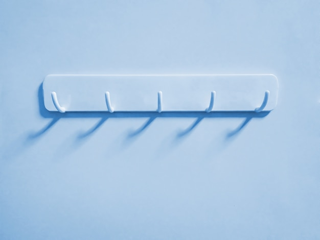 Голубые пластиковые крючки для подвешивания ткани на голубой стене