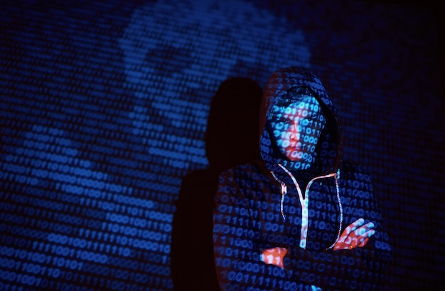Cyber attack with unrecognizable hooded hacker using virtual reality, digital glitch effect
