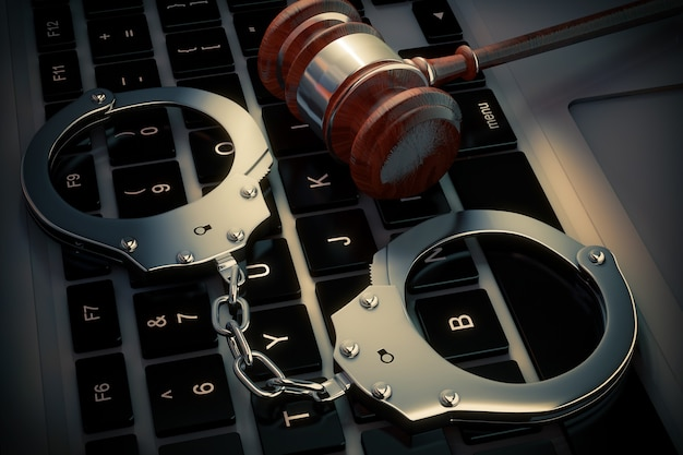 Cyber crime concept. handcuffs and judge gavel on laptop computer extreme closeup. 3d rendering