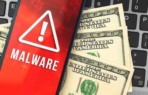 사이버 범죄 개념 사진, 노트북에 맬웨어와 돈이 있는 휴대폰, 해커 익명의 공격