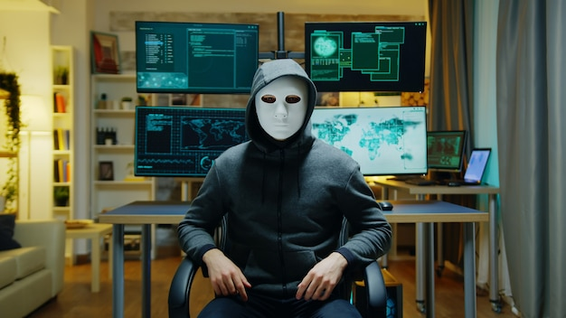 Cyber criminal wearing a white mask using augmented reality to steal secret information.