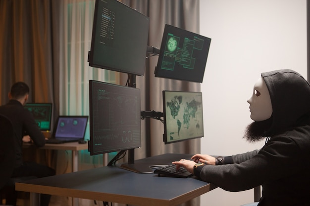 Criminale informatico che indossa una maschera bianca durante il test del sistema governativo. pirata informatico.