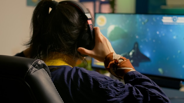 Кибер-геймер играет в космический шутер, используя клавиатуру rgb и профессиональную гарнитуру во время игрового турнира. игрок разговаривает с несколькими игроками в наушниках во время потоковой передачи видеоигр