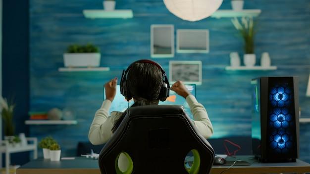 ゲームルームに座って、新しいグラフィックスで優勝したチャンピオンシップでビデオゲームをプレイするサイバーゲーマー。サイバースペースでの仮想宇宙シューティングゲーム、rgbプロフェッショナルコンピューティングでトーナメントを実行するeスポーツプレーヤー