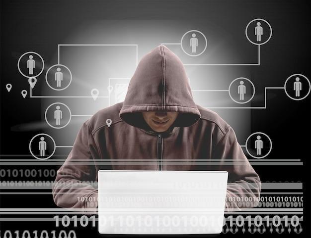 아이콘이 있는 어두운 배경에서 노트북을 사용하는 사이버 해커