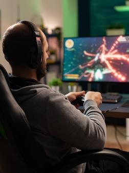 Кибер-человек с гарнитурой играет в соревновании с беспроводным контроллером в профессиональной студии. взволнованный игрок сидит на игровом стуле и смотрит в монитор, чтобы выиграть онлайн-чемпионат
