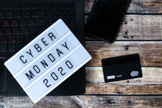 Cyber monday word written on lightbox on brown wood table. flat lay