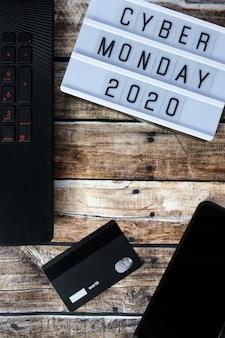 Слово cyber понедельник написано на лайтбоксе на коричневом деревянном столе. плоская планировка