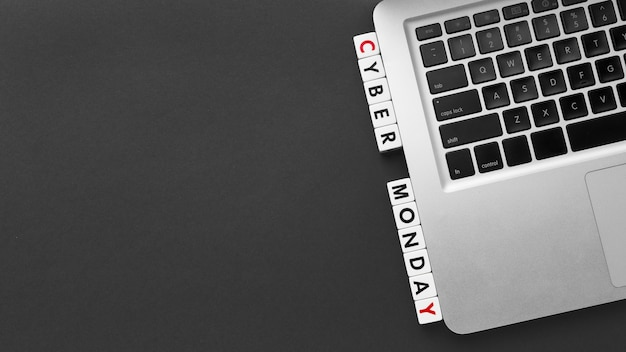 Cyber monday written with scrabble letters and laptop copy space
