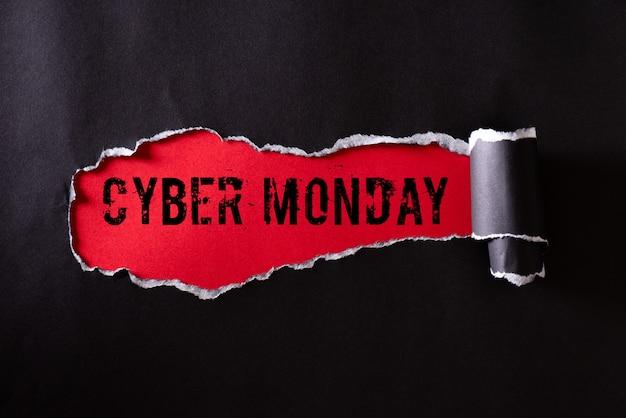 Черная рваная бумага и текст cyber monday на красном