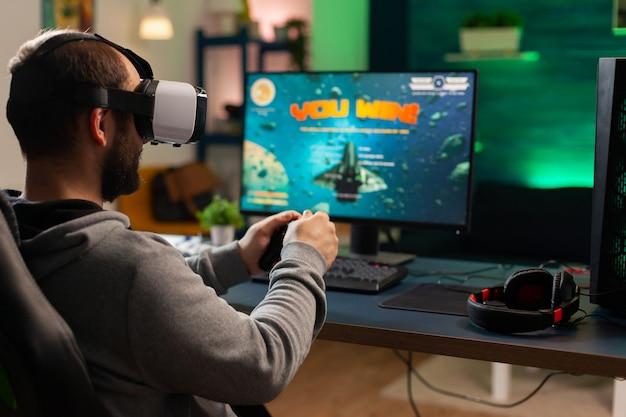 バーチャルリアリティヘッドセットを装着したサイバープロゲーマーがオンラインビデオゲームトーナメントで優勝。コンピューターで遊んでいるガミニングチェアに座ってスペースシューターチャンピオンシップのためにジョイパッドを使用しているプロのプレーヤー