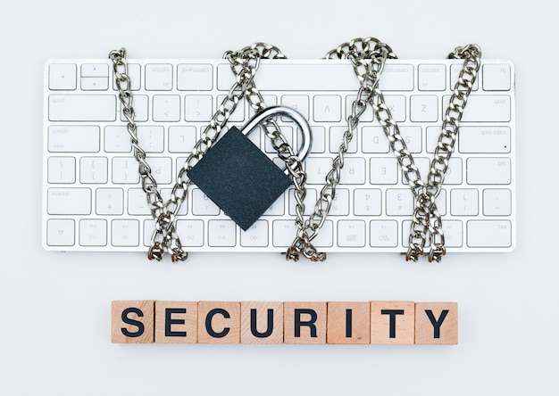 Cyber safety concept with chain and padlock on keyboard, wooden cubes on white background flat lay.