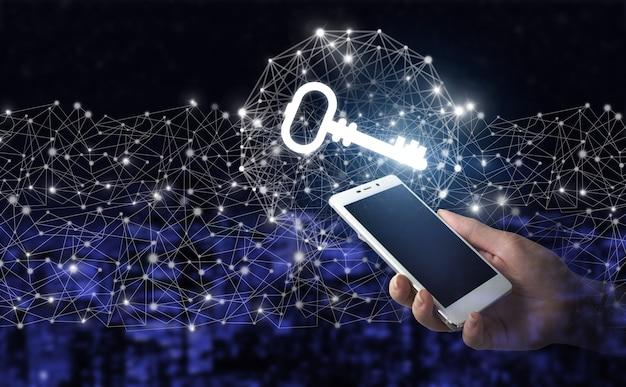 Сеть кибербезопасности. рука держать белый смартфон с цифровой голограммой ключевой знак на темном фоне размытым городом. концепция безопасности и защиты.