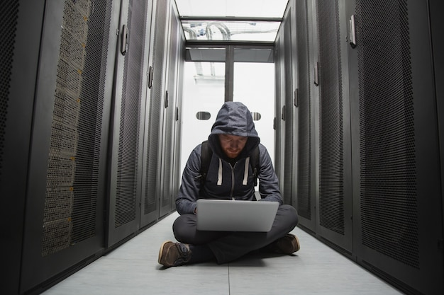 Cyber security. skilled male hacker sitting on floor while cracking system