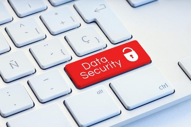 Слово кибербезопасности и значок замка на красной клавиатуре компьютера