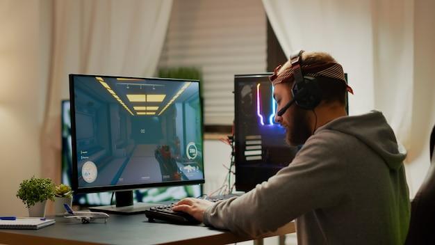 헤드폰을 착용한 사이버 스포츠 게이머는 e스포츠 토너먼트에 참가하여 rgb 성능이 뛰어난 개인용 컴퓨터에서 1인칭 슈팅 비디오 게임을 하고 있습니다. 프로 사이버 스트리밍 게임 챔피언십