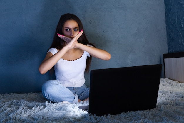 사이버 괴롭힘 개념. 노트북과 함께 침대에 앉아 십 대 피곤 된 소녀입니다.