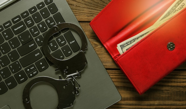Cybercrime, online digital theft. laptop with red purse and steel handcuffs on wooden table. top view