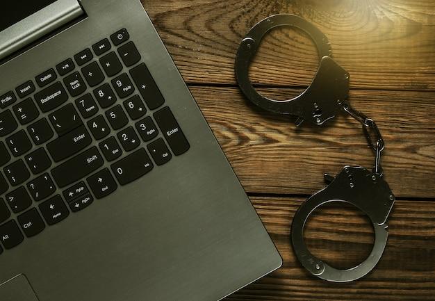 Киберпреступность, цифровая кража в интернете. ноутбук со стальными наручниками на деревянном столе. вид сверху