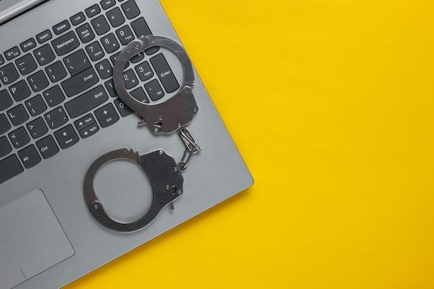 サイバー犯罪、オンラインデジタル盗難。黄色の背景に鋼の手錠とラップトップ。上面図