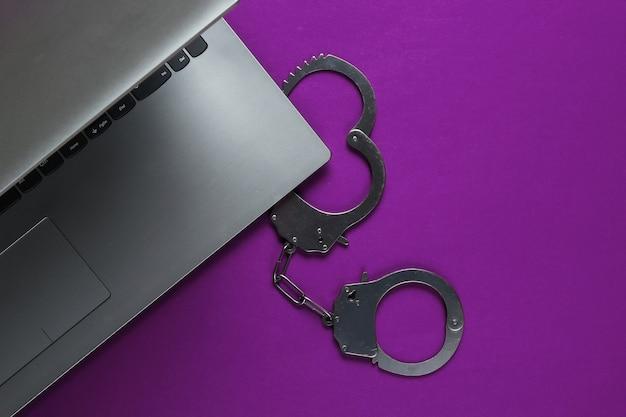 Киберпреступность, цифровая кража в интернете. ноутбук со стальными наручниками .. вид сверху