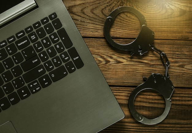 Cybercrime, online digital theft. laptop with steel handcuffs on wooden table. top view