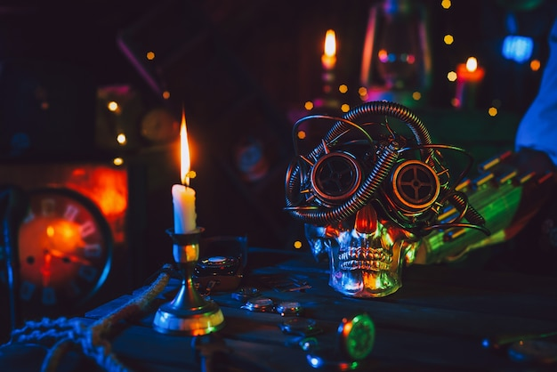 Cyberpunk atmosphere. skull in steampunk glasses on a table with mechanisms with neon colored light