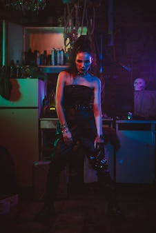 Cyberpunk cosplay. girl in a futuristic costume cosplay steampunk style. a woman with neon lights in a post-apocalyptic garage Premium Photo