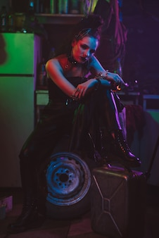 Cyberpunk cosplay. a girl in the steampunk style of the future smokes a cigarette in a post-apocalyptic style. garage with neon light