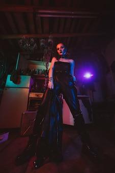 네온 조명이 있는 사이버펑크 여성 코스프레. 종말 이후의 세계에서 스팀펑크 의상을 입은 소녀