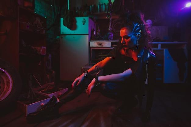 ネオン照明付きのガレージでスチームパンクな衣装を着たサイバーパンクの女の子。ポスト黙示録的なコスプレ