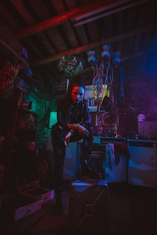 Cyberpunk girl in a post-apocalyptic futuristic style in a garage with a neon light. steampunk cosplay
