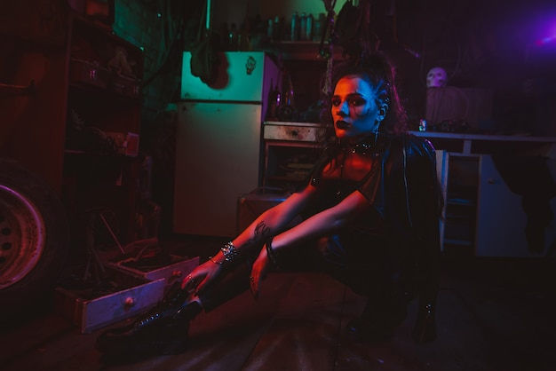 Cyberpunk girl in a steampunk costume in a garage with neon lighting. post-apocalyptic cosplay