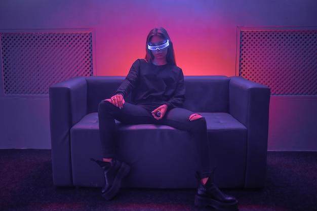 Киберпанк женщина, сидящая на софе с неоновыми очками. на фото эффект куш, зернистость.