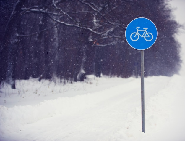 Cycle lane sign covered with snow against a dark forest