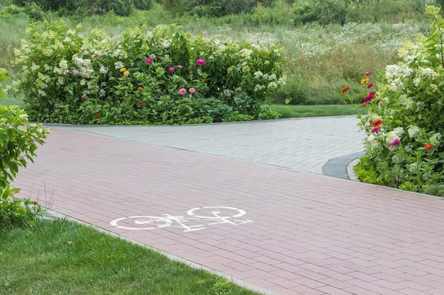 화단 사이 공원에서 자전거 경로입니다. 아스팔트에 자전거의 그림입니다.