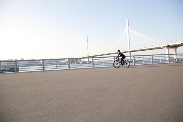 斜張橋を背景に堤防沿いをサイクリング