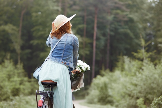 ファッションの女性による森のサイクリング