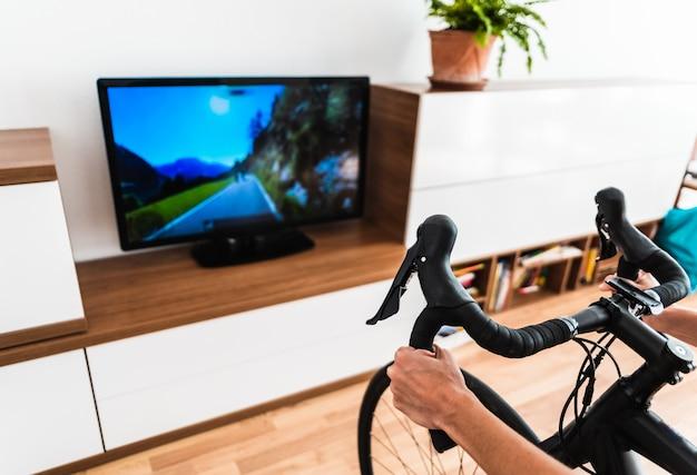 スポーツのゲーミフィケーションで自分自身をやる気にさせるエアロバイクトレーナーと一緒に屋内でサイクリング。