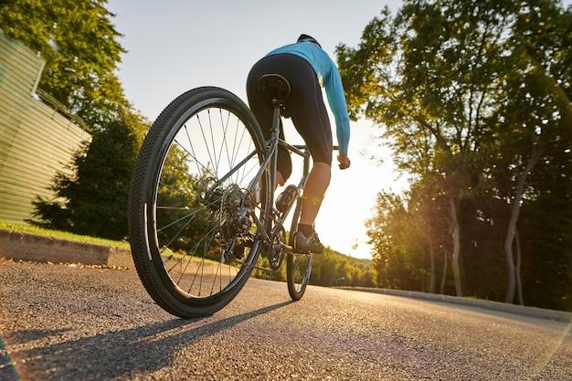 サイクリングは、彼の道路に乗っているプロの男性自転車レーサーの楽しいローアングルビューです