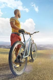 サイクリング。夏の日に山の林道で自転車を持つ男。日の出の間に山の谷