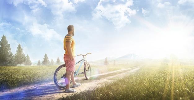 サイクリング。夏の日の山の林道で自転車を持った男。スポーツ。パノラマ