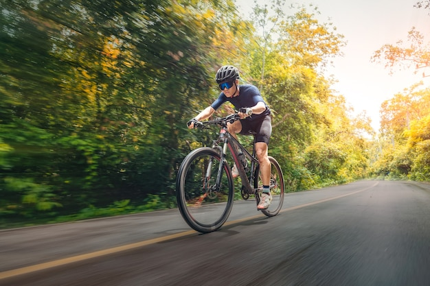 Cycling mountain bike cycling mtb on the road shady with forest. mountain biking athlete look at wild nature on mountain. extreme sport and mtb, mountain bike downhill of motion concept.