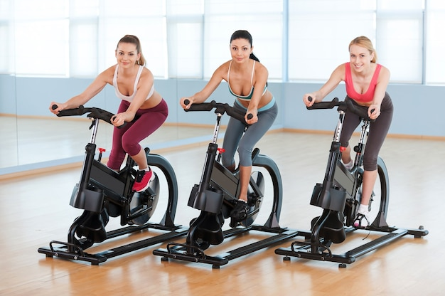 エアロバイクでのサイクリング。ジムの自転車で運動するスポーツウェアの2人の魅力的な若い女性