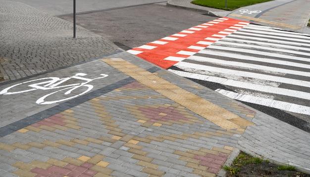 Avtomobile道路を通って地面に自転車のシンボルがあるサイクリングパス。近代的な都市の自転車道。