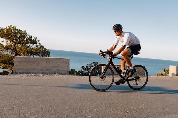夜明けに海岸道路に乗ってサイクリングスポーツアスリート男