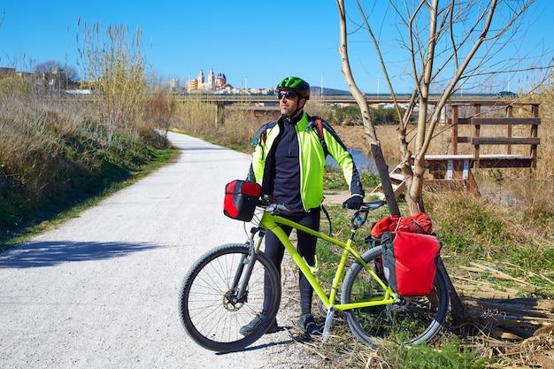 Cycling tourist cyclist in ribarroja turia with paniers