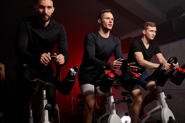 집중적으로 사이클링. 체육관에서 운동복 사이클링에 완벽한 몸매를 가진 젊은 백인 남자