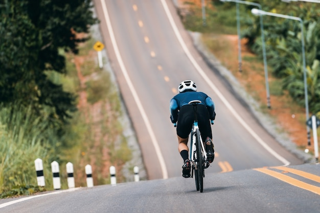 Cyclist adjusting posture to reduce air resistance. in the bike down the hill.